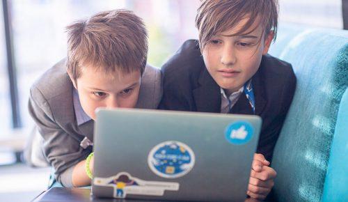 Två pojkar tittar på en bärbar dator.