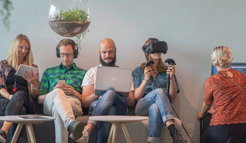 Fem människor som använder olika digitala enheter