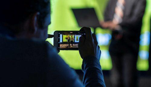 En man tar en bild med sin mobiltelefon på en presentation på en scen.