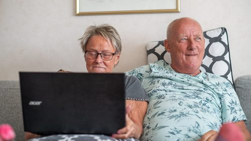 Äldre par sitter i en soffa med en en bärbar dator i knäet.