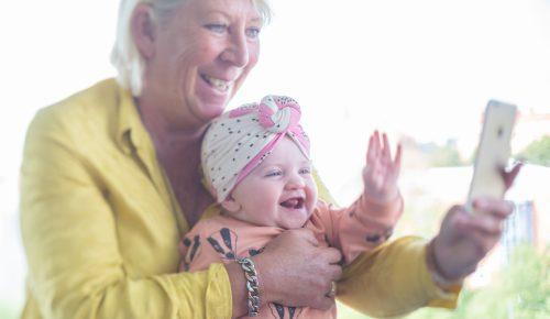Kvinna och bebis tar bild tillsammans med en mobilkamera och skrattar.