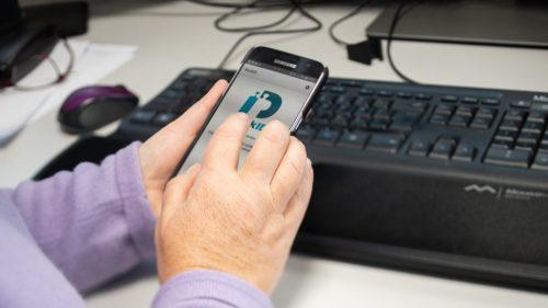 Händer håller mobil med mobilt BankID.