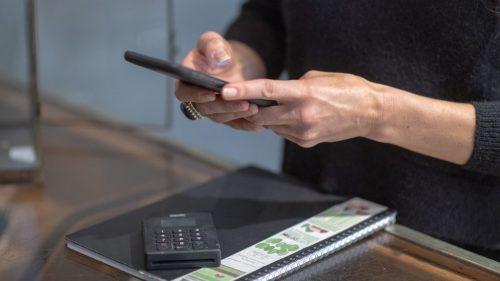 Händer håller en mobiltelefon vid ett bord.