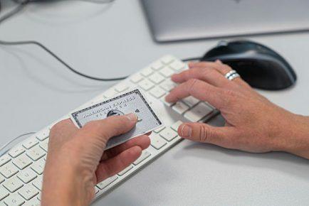 Hand håller i ett American Express medan den andra handen knappar in kortuppgifterna på ett tangentbord