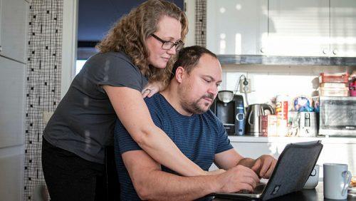 Kvinna och man tittar på dator i kök.