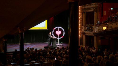 Måns Jonasson står på en scen och presenterar Svenskarna och internet 2019.