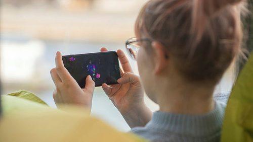 Kvinna spelar på sin mobil.