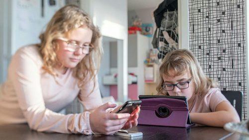 En flicka surfar på en mobil och en flicka tittar på en surfplatta hemma i köksmiljö.