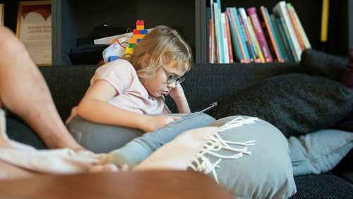 Ett barn sitter i en soffa och tittar ner på en padda.