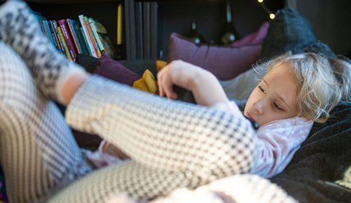 Barn använder surfplatta i soffa.