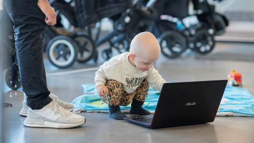 Bebis sitter på huk på golvet framför en bärbar dator.