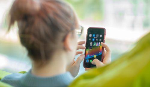 kvinna sitter med mobil för att spela