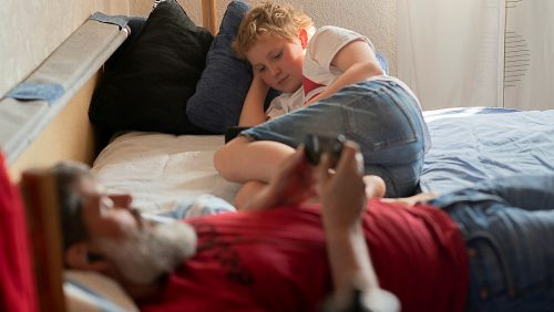 Pappa och son ligger i en säng och surfar på surfplatta och mobiltelefon.