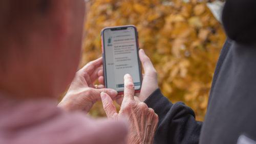 Äldre och yngre händer håller i en mobiltelefon med mobilt bank-id tillsammans