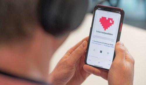En man med hörlurar håller i en mobiltelefon med Internetpodden framme