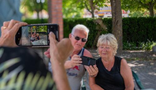 Äldre par med mobiltelefon, fotograferas av annan mobiltelefon.