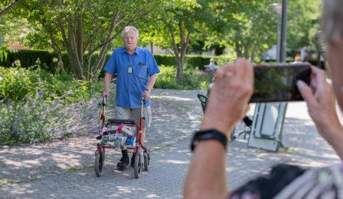 En äldre man promenerar med en rullator och någon fotografera honom med en mobiltelefon