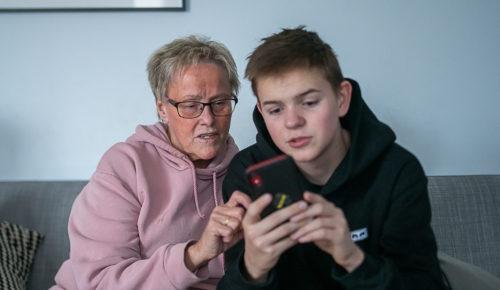 Pojke visar äldre kvinna något på sin mobiltelefon