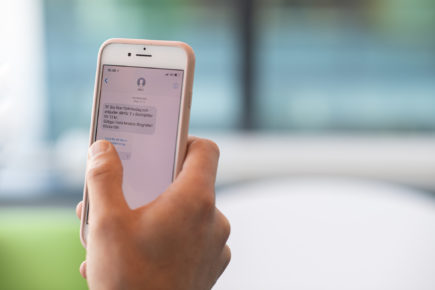 En hand håller i en mobiltelefon med ett bedrägerisms från SF Bio