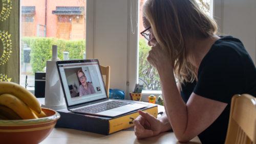 Kvinna sitter vid sitt köksbord och har videokonferensmöte med en annan kvinna.