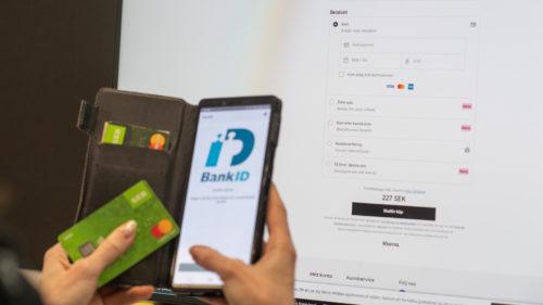 Någon sitter framför datorskärm och betalar för nätshopping med hjälp av mobilt bank-id