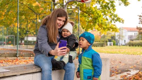 En mamma och två barn pratar har ett videosamtal via mobilen utomhus.