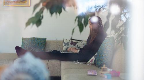 En kvinna sitter i en soffa och skriver på sin laptop i knäet.