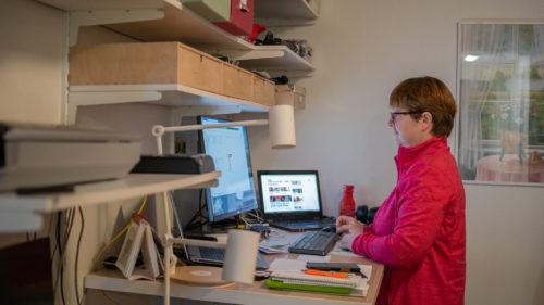 En kvinna står upp och arbetar vid sin dator på sitt hemmakontor.