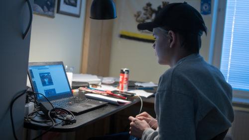 En kille med keps sitter framför sin dator vid ett skrivbord i sitt rum hemma och studerar