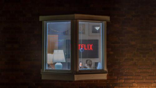 En kvinna sitter i sin soffa framför Netflix på tv:n