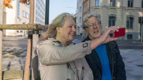 Äldre par tar en selfie tillsammans med mobiltelefonen sittandes utomhus.