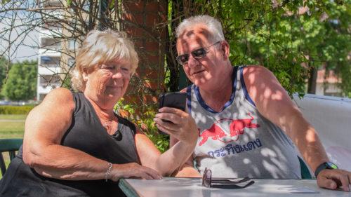 Äldre par sitter i park och tittar gemensamt på en mobiltelefon