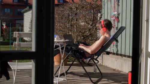 Kille sitter i solen i en solstol och studerar med sin laptop i knäet